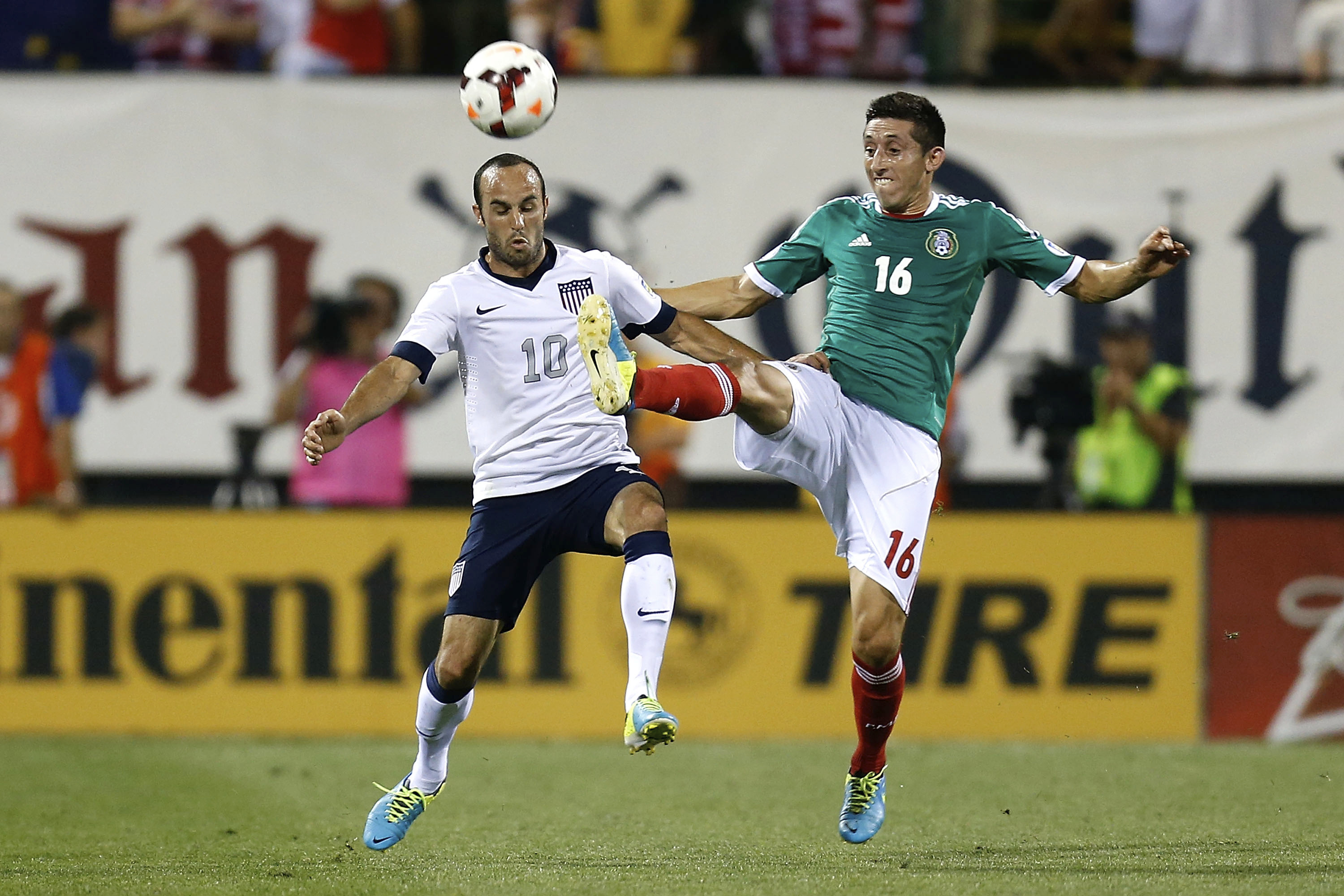 COLUMBUS, UNITED STATES - SEPTEMBER 10: Landon Donovan of the US and Hector Herrera of Mexico fight for the ball during a match between United States and Mexico as part of the CONCACAF Qualifiers at Columbus Crew Stadium on September 10, 2013 in Columbus, United States.